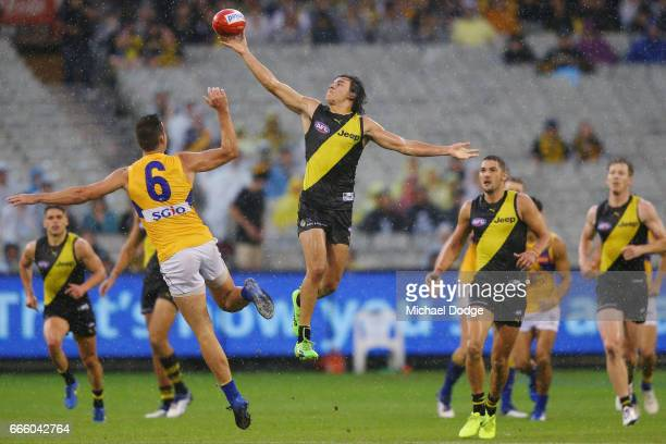 Daniel Rioli of the Tigers taps the ball over Elliot Yeo of the Eagles during the round three AFL match between the Richmond Tigers and the West...