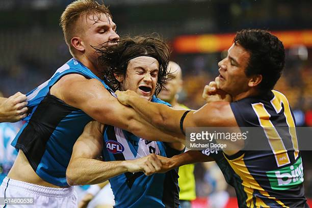 Daniel Rioli of the Tigers wrestles with Jasper Pittard and Ollie Wines of the Power during the 2016 AFL NAB Challenge match between the Richmond...