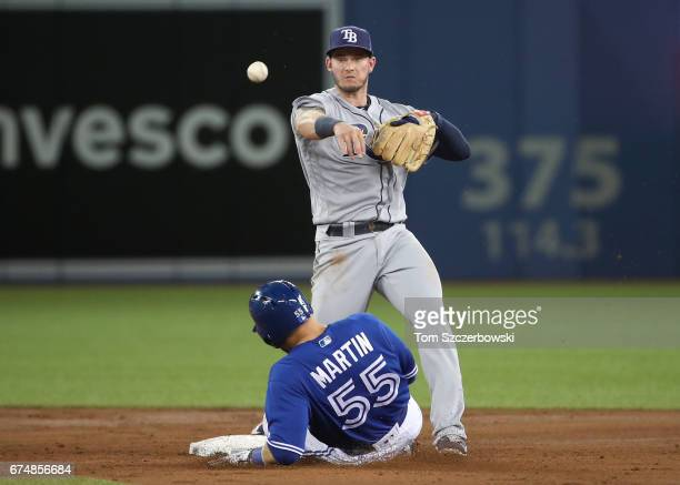 Daniel Robertson of the Tampa Bay Rays gets the force out of Russell Martin of the Toronto Blue Jays at second base but cannot turn the double play a...