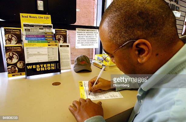 Daniel Salcedo fills out a form to wire money at a Western Union outlet in San Diego California February 3 2004 First Data Corp parent of the world's...