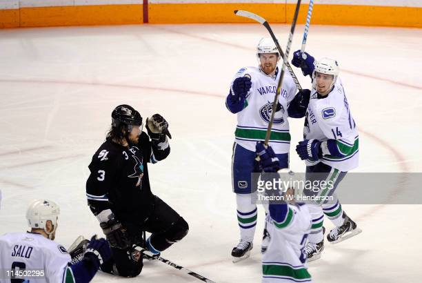 Daniel Sedin and Alex Burrows of the Vancouver Canucks celebrate teammate Sami Salo's first of two second period goals as Douglas Murray of the San...