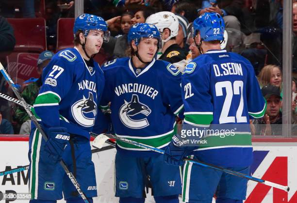 Daniel Sedin and Ben Hutton of the Vancouver Canucks congratulate teammate Markus Granlund after scoring during their NHL game against the Boston...