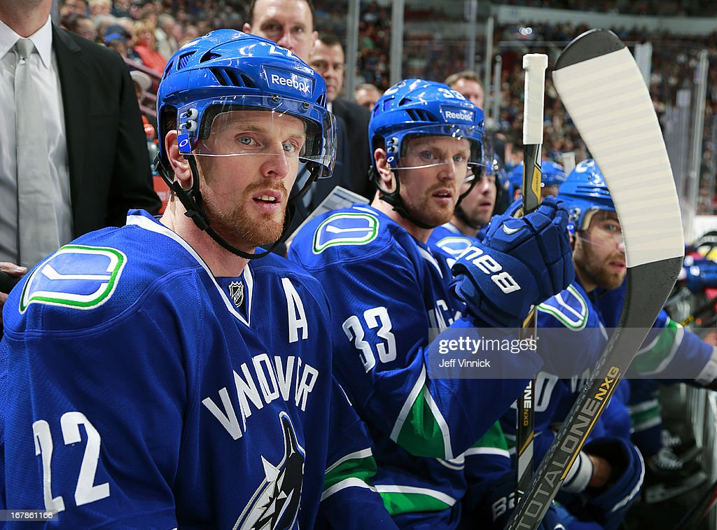 Daniel Sedin #22 and Henrik Sedin #33 of the Vancouver Canucks look on from the bench during their NHL game against the Anaheim Ducks at Rogers Arena April 25, 2013 in Vancouver, British Columbia, Canada. Anaheim won 3-1.