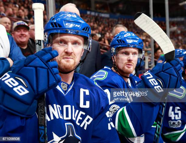 Daniel Sedin and Henrik Sedin of the Vancouver Canucks look on from the bench during their NHL game against the Los Angeles Kings at Rogers Arena...