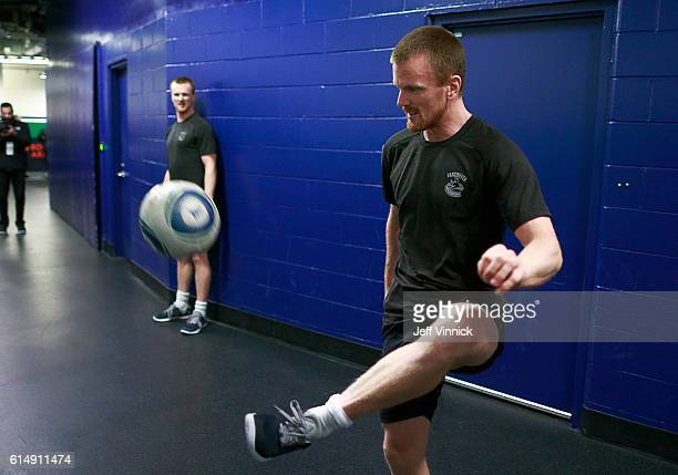Daniel Sedin looks on as teammate Henrik Sedin of the Vancouver Canucks kicks a soccer ball before their NHL game against the Calgary Flames at...