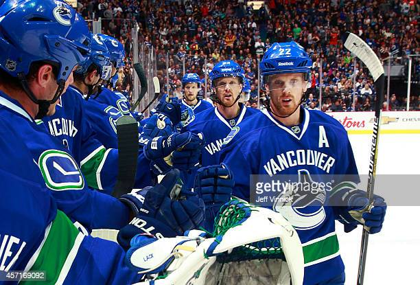 Daniel Sedin of and Henrik Sedin of the Vancouver Canucks are congratulated after scoring during their NHL game against the Edmonton Oilers at Rogers...