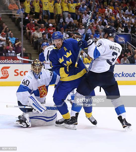 Daniel Sedin of Team Sweden battles for position with Olli Maatta in front of Tuukka Rask of Team Finland during the World Cup of Hockey 2016 at Air...