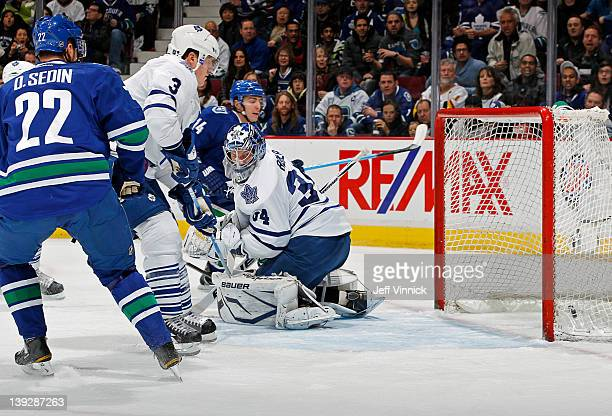 Daniel Sedin of the Vancouver Canucks and Dion Phaneuf of the Toronto Maple Leafs watch as Alex Burrows of the Canucks beats James Reimer of the...
