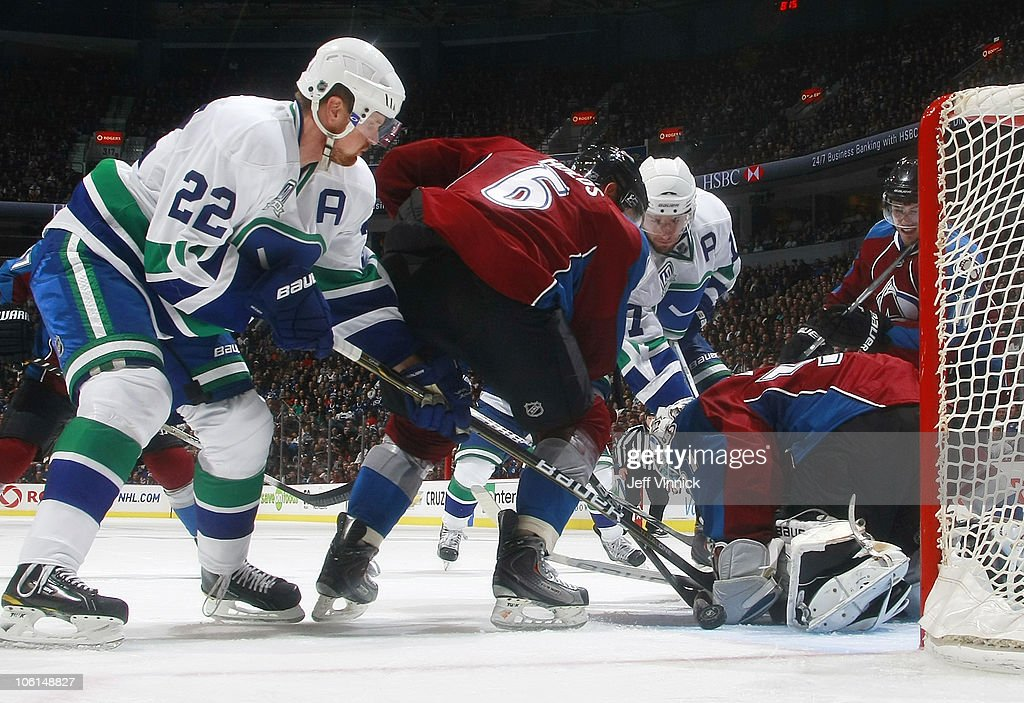 <a gi-track='captionPersonalityLinkClicked' href=/galleries/search?phrase=Daniel+Sedin&family=editorial&specificpeople=202492 ng-click='$event.stopPropagation()'>Daniel Sedin</a> #22 of the Vancouver Canucks and Jonas Holos #6 of the Colorado Avalanche look on as <a gi-track='captionPersonalityLinkClicked' href=/galleries/search?phrase=Ryan+Kesler&family=editorial&specificpeople=206915 ng-click='$event.stopPropagation()'>Ryan Kesler</a> #17 of the Vancouver Canucks scores on <a gi-track='captionPersonalityLinkClicked' href=/galleries/search?phrase=Peter+Budaj&family=editorial&specificpeople=228123 ng-click='$event.stopPropagation()'>Peter Budaj</a> #31 of the Colorado Avalanche at Rogers Arena on October 26, 2010 in Vancouver, British Columbia, Canada. Vancouver won 4-3 in overtime.