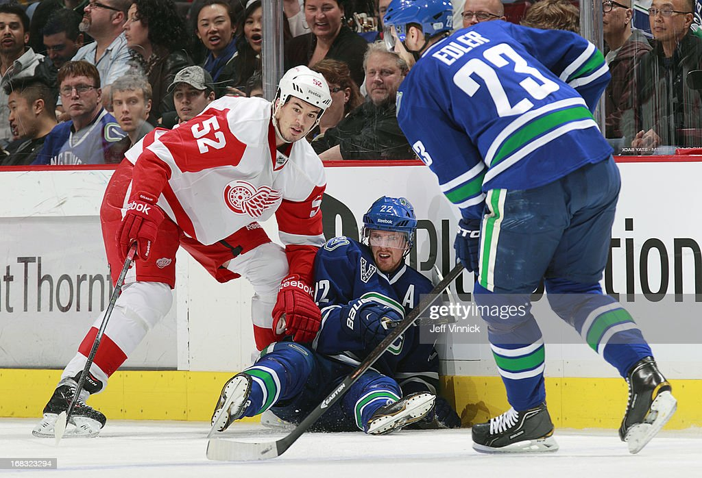 Daniel Sedin #22 of the Vancouver Canucks and Jonathan Ericsson #52 of the Detroit Red Wings look on as Alexander Edler #23 of the Vancouver Canucks skates up ice with the puck during their NHL game at Rogers Arena April 20, 2013 in Vancouver, British Columbia, Canada. Vancouver won 2-1.