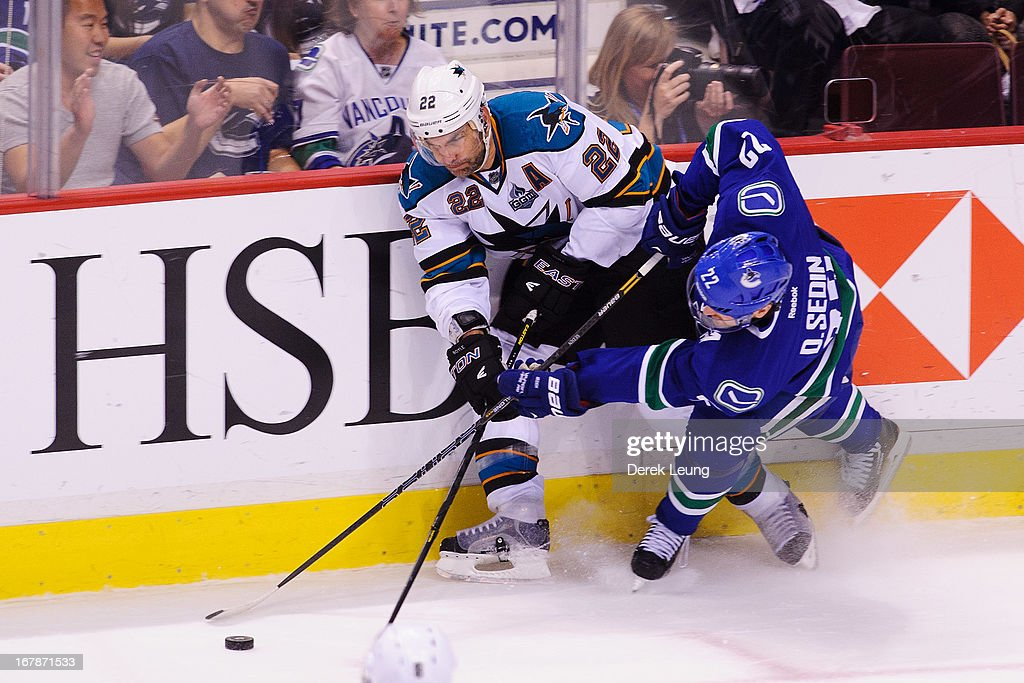 <a gi-track='captionPersonalityLinkClicked' href=/galleries/search?phrase=Daniel+Sedin&family=editorial&specificpeople=202492 ng-click='$event.stopPropagation()'>Daniel Sedin</a> #22 of the Vancouver Canucks battles for the puck against <a gi-track='captionPersonalityLinkClicked' href=/galleries/search?phrase=Dan+Boyle&family=editorial&specificpeople=201502 ng-click='$event.stopPropagation()'>Dan Boyle</a> #22 of the San Jose Sharks in Game One of the Western Conference Quarterfinals during the 2013 NHL Stanley Cup Playoffs at Rogers Arena on May 1, 2013 in Vancouver, British Columbia, Canada. The San Jose Sharks won 3-1.