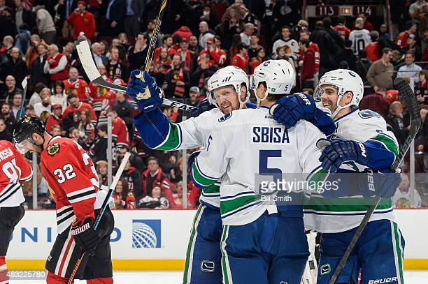 Daniel Sedin of the Vancouver Canucks celebrates with Luca Sbisa and Dan Hamhuis after scoring the game winning goal in overtime against the Chicago...