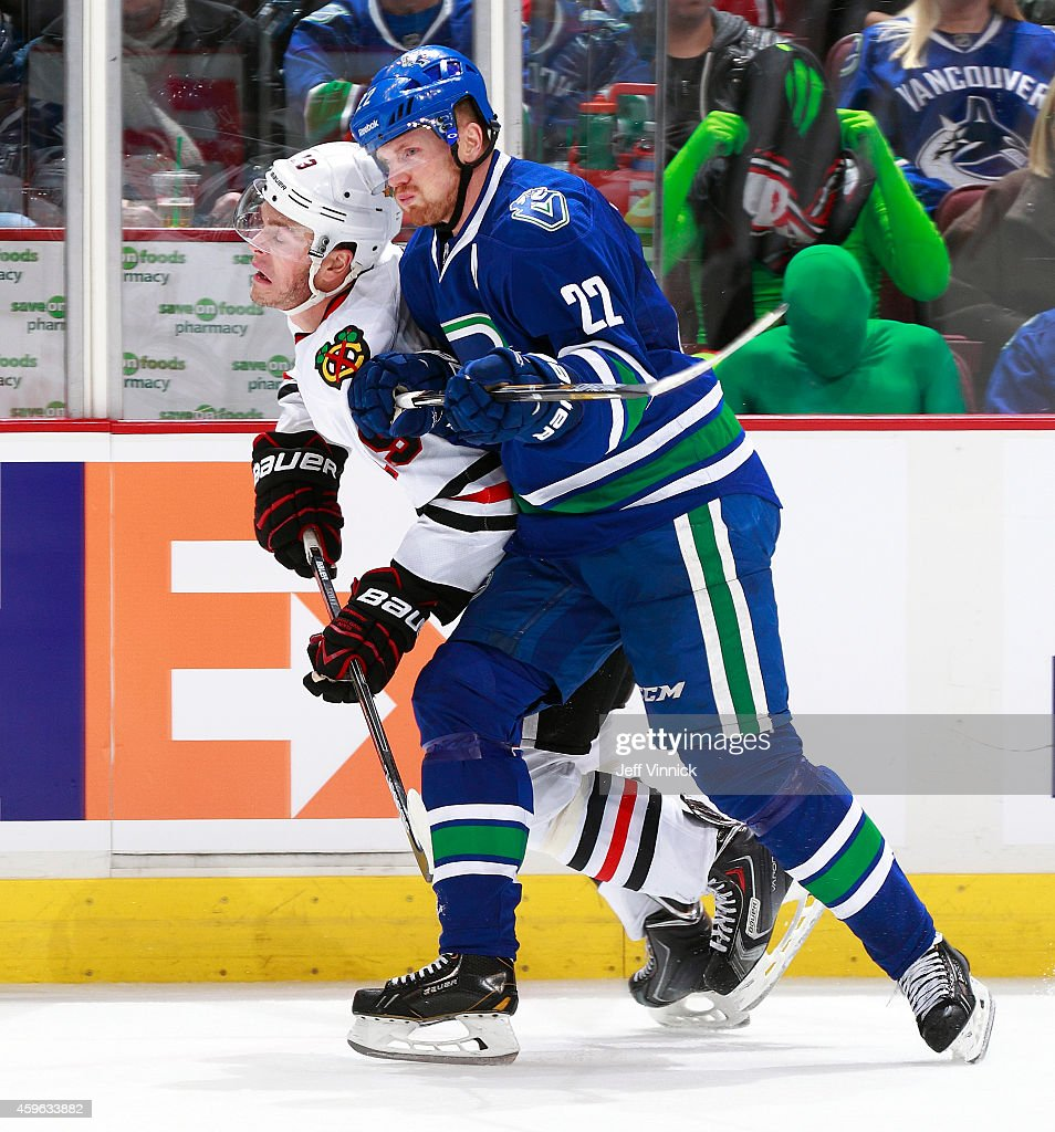 <a gi-track='captionPersonalityLinkClicked' href=/galleries/search?phrase=Daniel+Sedin&family=editorial&specificpeople=202492 ng-click='$event.stopPropagation()'>Daniel Sedin</a> #22 of the Vancouver Canucks checks <a gi-track='captionPersonalityLinkClicked' href=/galleries/search?phrase=Jonathan+Toews&family=editorial&specificpeople=537799 ng-click='$event.stopPropagation()'>Jonathan Toews</a> #19 of the Chicago Blackhawks during their NHL game at Rogers Arena November 23, 2014 in Vancouver, British Columbia, Canada.