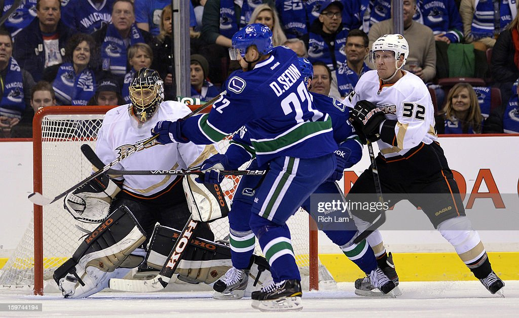 Daniel Sedin #22 of the Vancouver Canucks deflects the puck on goalie Jonas Hiller #1 of the Anaheim Ducks during the first period in NHL action on January 19, 2013 at Rogers Arena in Vancouver, British Columbia, Canada. Toni Lydman #32 of the Anaheim Ducks tries to help defend on the play.