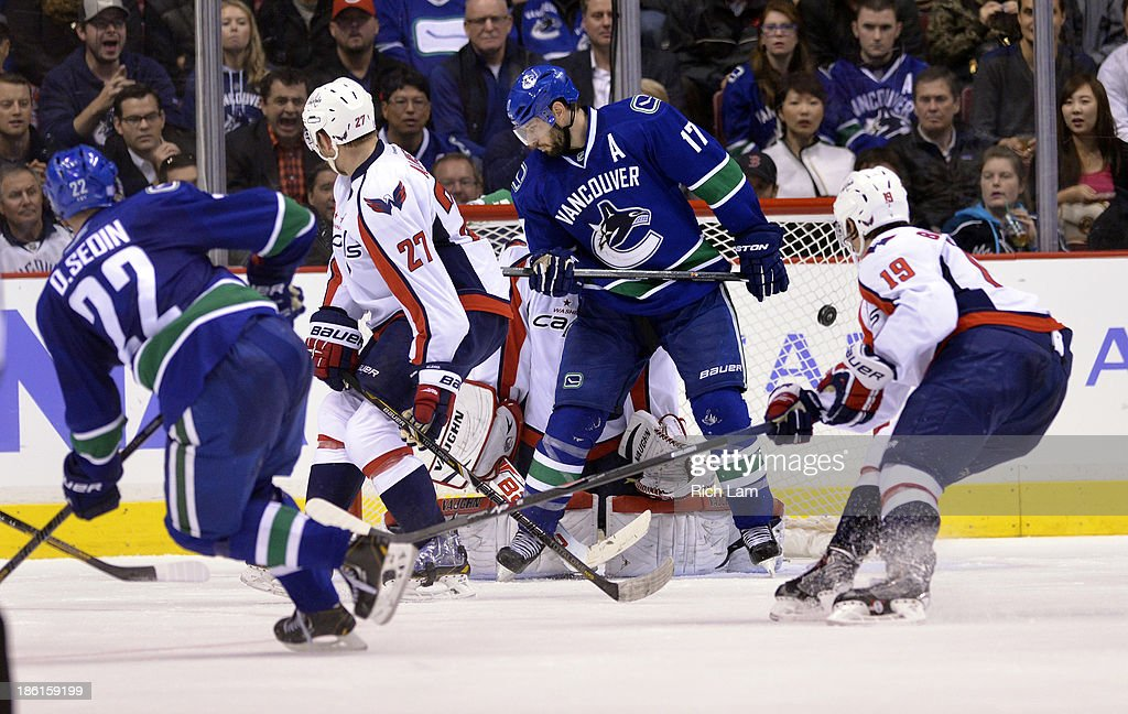 <a gi-track='captionPersonalityLinkClicked' href=/galleries/search?phrase=Daniel+Sedin&family=editorial&specificpeople=202492 ng-click='$event.stopPropagation()'>Daniel Sedin</a> #22 of the Vancouver Canucks fires a slap shot past goalie <a gi-track='captionPersonalityLinkClicked' href=/galleries/search?phrase=Michal+Neuvirth&family=editorial&specificpeople=3205600 ng-click='$event.stopPropagation()'>Michal Neuvirth</a> #30 of the Washington Capitals for what proved to be the game winning goal during the third period in NHL action on October 28, 2012 at Rogers Arena in Vancouver, British Columbia, Canada. <a gi-track='captionPersonalityLinkClicked' href=/galleries/search?phrase=Ryan+Kesler&family=editorial&specificpeople=206915 ng-click='$event.stopPropagation()'>Ryan Kesler</a> #17 of the Vancouver Canucks looks on with <a gi-track='captionPersonalityLinkClicked' href=/galleries/search?phrase=Karl+Alzner&family=editorial&specificpeople=3938829 ng-click='$event.stopPropagation()'>Karl Alzner</a> #27 and Nicklas Backstrom #19 of the Washington Capitals.