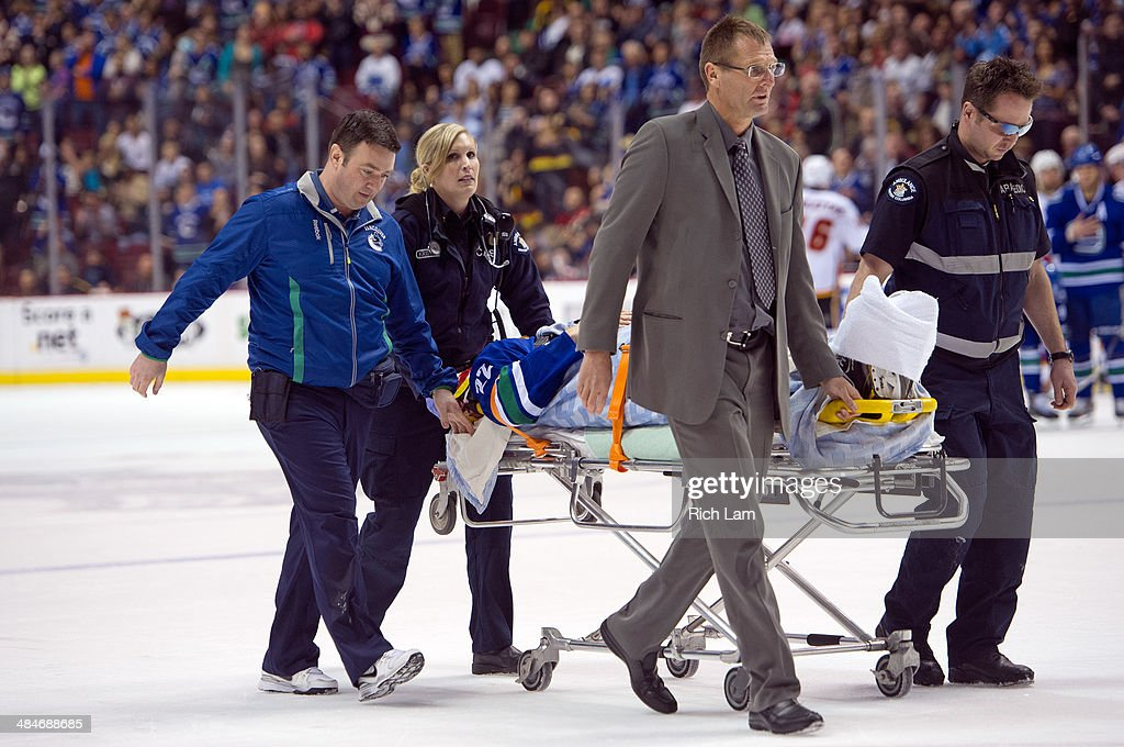 Daniel Sedin #22 of the Vancouver Canucks is wheeled off on a stretcher by medical staff after getting hit by Paul Byron (not pictured) of the Calgary Flames during the second period in NHL action on April 13, 2014 at Rogers Arena in Vancouver, British Columbia, Canada.