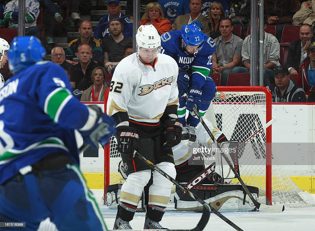 Daniel Sedin #22 of the Vancouver Canucks leaps to avoid a shot and Toni Lydman #32 of the Anaheim Ducks looks down on what was a goal during their NHL game at Rogers Arena April 25, 2013 in Vancouver, British Columbia, Canada. Anaheim won 3-1.