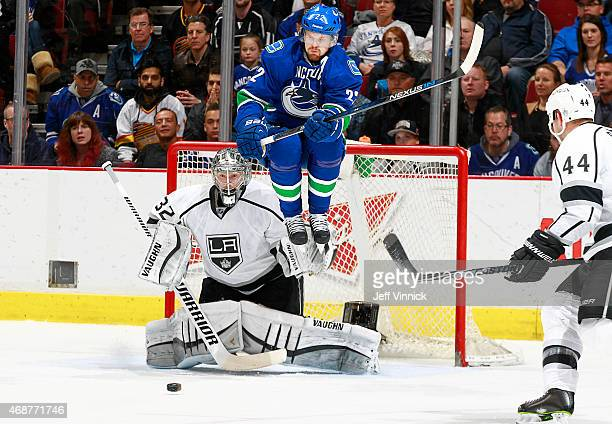 Daniel Sedin of the Vancouver Canucks leaps to avoid the puck in front of Jonathan Quick and Robyn Regehr of the Los Angeles Kings during their NHL...