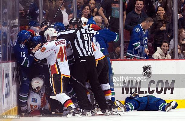 Daniel Sedin of the Vancouver Canucks lies on the ice as players from the Vancouver Canucks and the Calgary Flames push and shove during the second...