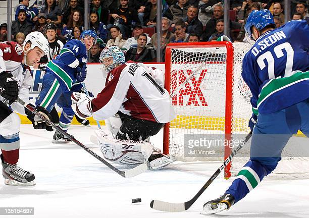 Daniel Sedin of the Vancouver Canucks lines up his third goal of the game while Shane O'Brien and Semyon Varlamov of the Colorado Avalanche and Alex...