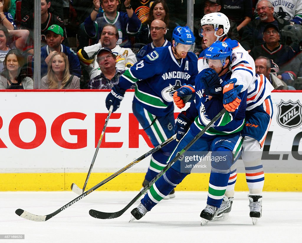 Daniel Sedin of the Vancouver Canucks looks on as David Perron of the Edmonton Oilers checks Henrik Sedin of the Vancouver Canucks during their NHL...