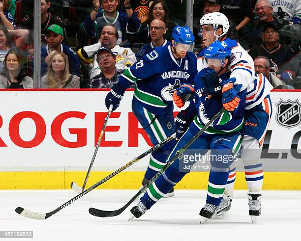 Daniel Sedin of the Vancouver Canucks looks on as David Perron of the Edmonton Oilers checks Henrik Sedin of the Vancouver Canucks during their NHL...