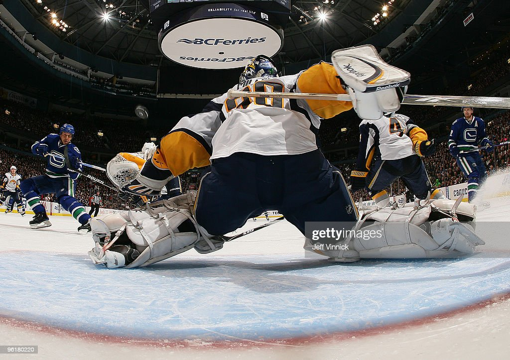 Daniel Sedin of the Vancouver Canucks looks on as teammate Brad Lukowich shoots the puck past Ryan Miller of the Buffalo Sabres for the game winning...
