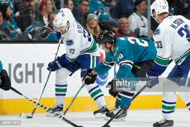 Daniel Sedin of the Vancouver Canucks moves the puck along the boards as Timo Meier of the San Jose Sharks defends at SAP Center at San Jose on April...