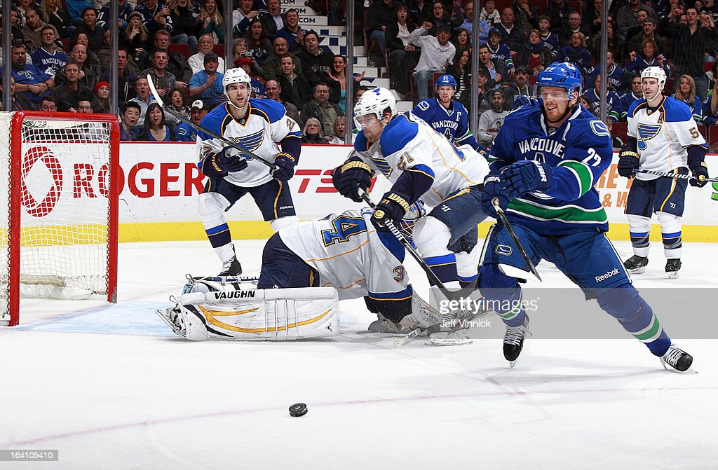 Daniel Sedin #22 of the Vancouver Canucks reaches for the puck while Patrik Berglund #21 of the St. Louis Blues scrambles in front of goalie Jake Allen #34 of the Blues during their NHL game at Rogers Arena March 19, 2013 in Vancouver, British Columbia, Canada.