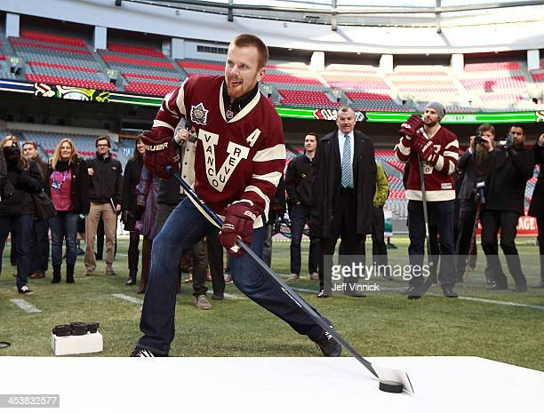 Daniel Sedin of the Vancouver Canucks shoots a puck through the football goal posts at BC Place during a media availability for the 2014 Tim Hortons...