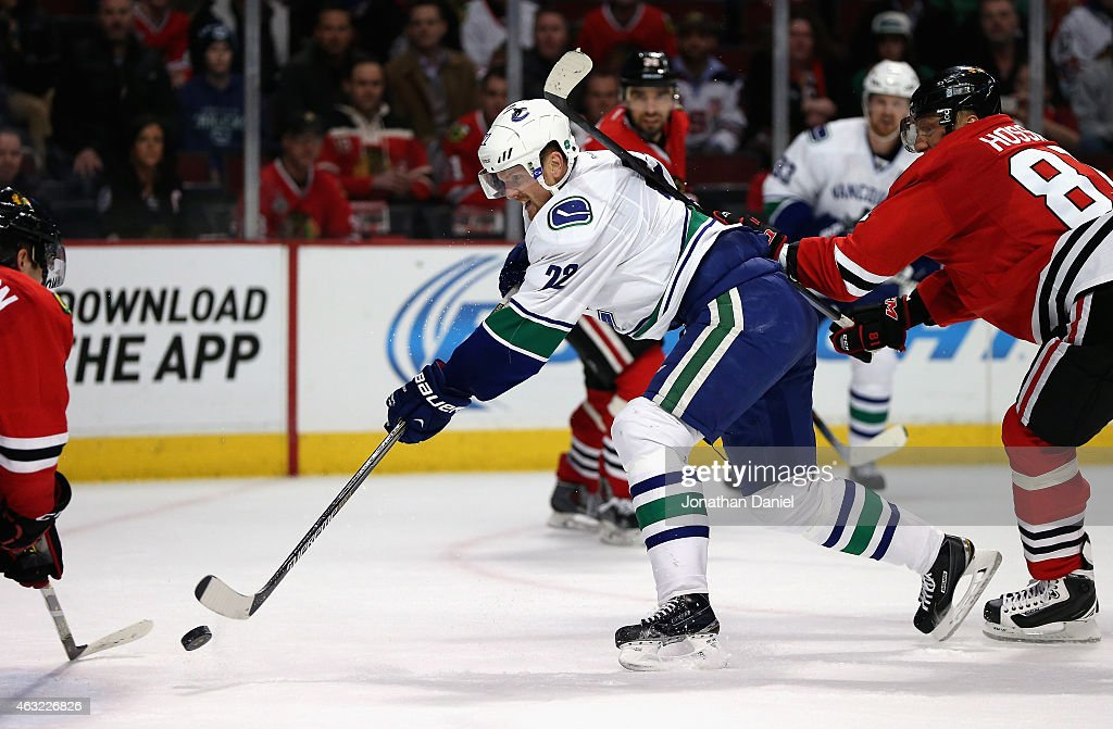 <a gi-track='captionPersonalityLinkClicked' href=/galleries/search?phrase=Daniel+Sedin&family=editorial&specificpeople=202492 ng-click='$event.stopPropagation()'>Daniel Sedin</a> #22 of the Vancouver Canucks shoots the game-winning goal under pressure from <a gi-track='captionPersonalityLinkClicked' href=/galleries/search?phrase=Marian+Hossa&family=editorial&specificpeople=202233 ng-click='$event.stopPropagation()'>Marian Hossa</a> #81 of the Chicago Blackhawks at the Chicago Blackhawks at the United Center on February 11, 2015 in Chicago, Illinois. The Canucks defeated the Blackhawks 5-4 in overtime.