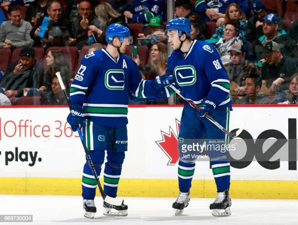 Daniel Sedin of the Vancouver Canucks talks to teammate Nikita Tryamkin during their NHL game against the Anaheim Ducks at Rogers Arena March 28 2017...