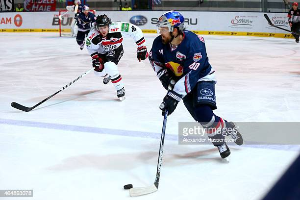 Daniel Sparre of Muenchen is challenge by Ryan Jones of Koeln during the DEL Ice Hockey match between EHC Red Bull Muenchen and Koelner Haie at...