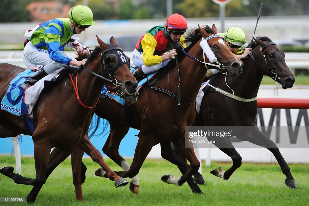 Daniel Stackhouse riding Weinholt (CTR) wins from Chad Schofield riding Churchill Dancer (L) and Damian Lane rinding Hard Stride (R) in the Geoff Murphy Handicap during Melbourne Racing at Caulfield Racecourse on March 30, 2013 in Melbourne, Australia.