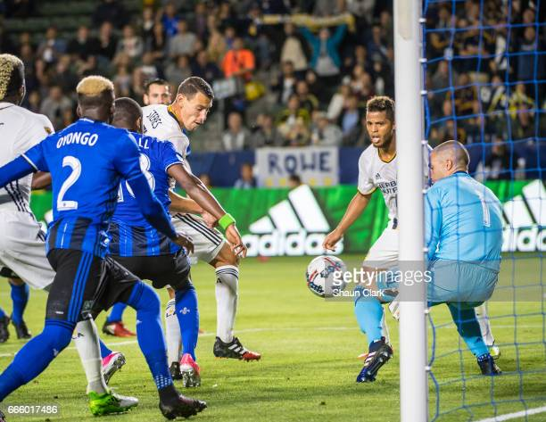 Daniel Steres of Los Angeles Galaxy kicks the ball toward goal as Evan Bush of Montreal Impact defends during Los Angeles Galaxy's MLS match against...