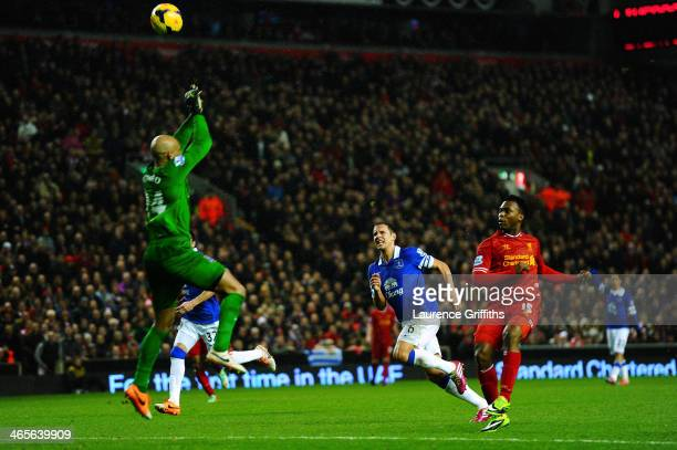 Daniel Sturridge of Liverpool chips the ball over goalkeeper Tim Howard of Everton to score his team's third goal during the Barclays Premier League...