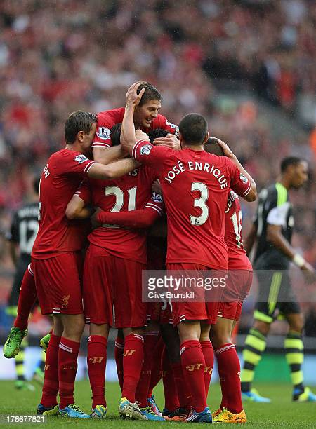 Daniel Sturridge of Liverpool is congratulated by Iago AspasLucasPhiluppe CoutinhoSteven Gerrard and Kolo Toure after scoring the first goal during...