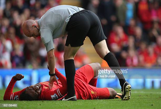 Daniel Sturridge of Liverpool lies injured and is checked by the referee Mr A Taylor during the Barclays Premier League match between Liverpool and...