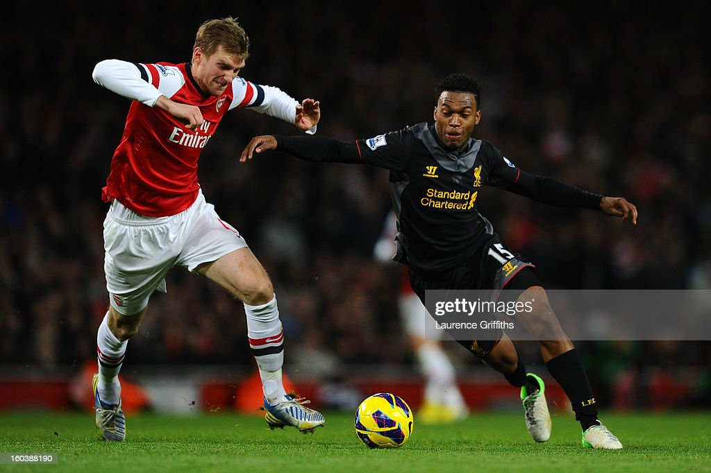 Daniel Sturridge of Liverpool loses his boot as he battle for the ball with Per Mertesacker of Arsenal during the Barclays Premier League match between Arsenal and Liverpool at Emirates Stadium on January 30, 2013 in London, England.