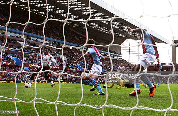Daniel Sturridge of Liverpool rounds goalkeeper Brad Guzan of Aston Villa to score the opening goal during the Barclays Premier League match between...