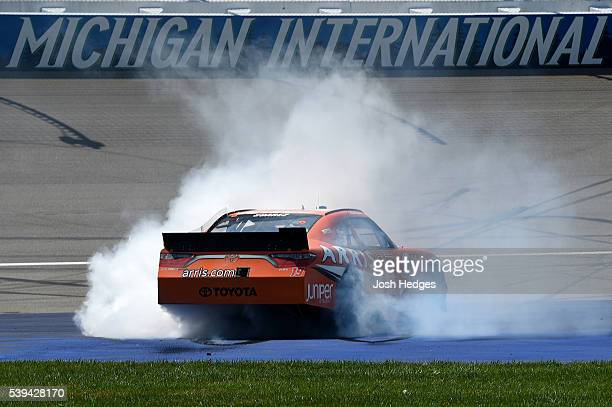 Daniel Suarez driver of the ARRIS Toyota celebrates with a burnout after winning the NASCAR XFINITY Series Menards 250 at Michigan International...
