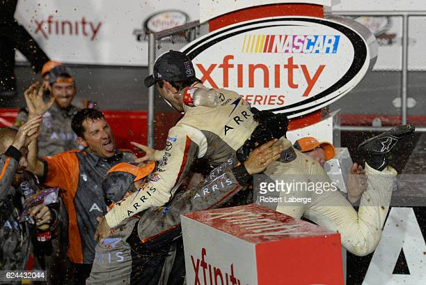 Daniel Suarez driver of the ARRIS Toyota celebrates with crew members in Victory Lane after winning the NASCAR XFINITY Series Ford EcoBoost 300 and...