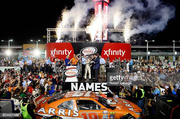 Daniel Suarez driver of the ARRIS Toyota is presented with the NASCAR XFINITY Series Championship trophy by NASCAR vice chairman Mike Helton in...