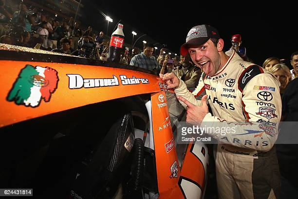 Daniel Suarez driver of the ARRIS Toyota poses with the championship decal in Victory Lane after winning the NASCAR XFINITY Series Ford EcoBoost 300...