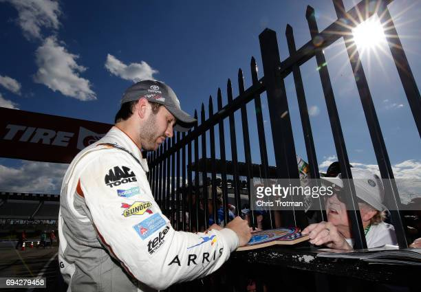 Daniel Suarez driver of the ARRIS Toyota signs autographs for fans during qualifying for the Monster Energy NASCAR Cup Series Axalta presents the...