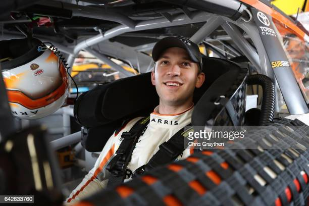 Daniel Suarez driver of the ARRIS Toyota sits in his car in the garage area during practice for the Monster Energy NASCAR Cup Series 59th Annual...