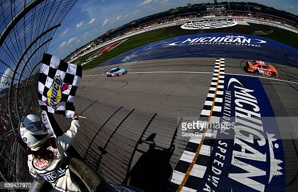 Daniel Suarez driver of the ARRIS Toyota takes the checkered flag ahead of Kyle Busch driver of the NOS Energy Drink Toyota to win the NASCAR XFINITY...