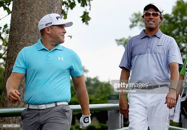 Daniel Summerhays and Stephen Ames of Canada walk off the first tee during the first round of the Greenbrier Classic at the Old White TPC on July 3...
