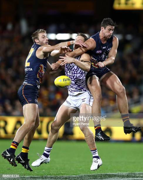 Daniel Talia and Kyle Hartigan of the Crows competes for the ball against Matt Taberner of the Dockers during the round 10 AFL match between the...