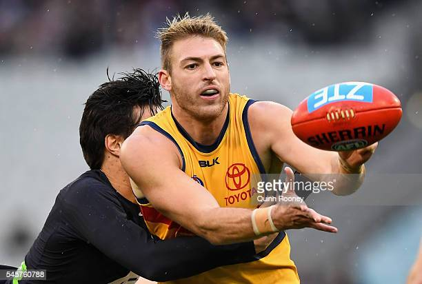 Daniel Talia of the Crows handballs whilst being tackled by Jack Silvagni of the Blues during the round 16 AFL match between the Carlton Blues and...